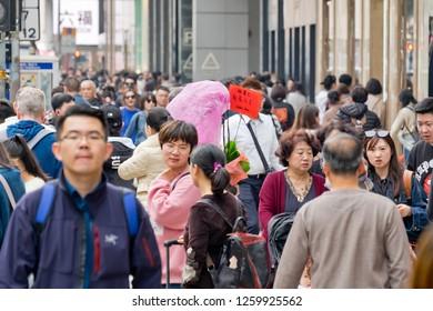 Tsim Sha Tsui, Hong Kong - 15 December, 2018 :  People walking across Canton Road Kowloon, Hong Kong. Canton Road is a major road in Hong Kong.