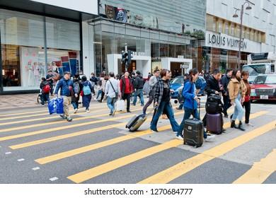 Tsim Sha Tsui, Hong Kong - 29 December, 2018 :  People walking across Canton Road Kowloon, Hong Kong. Canton Road is a major road in Hong Kong.