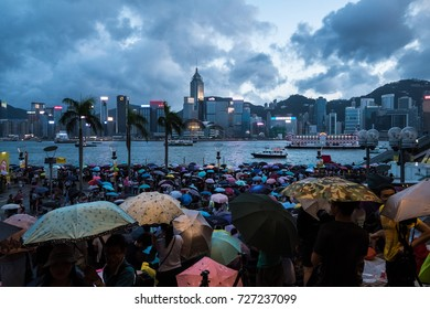 Tsim Sha Tsui, Kowloon, Hong Kong - 2 October 2017 :  Crowded people waiting National Day Fireworks Display in rain at waterfront of Victoria Harbour at evening
