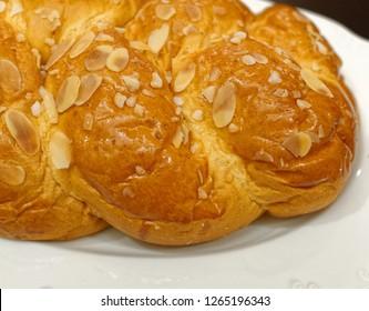 """tsoureki"" traditional Greek Christmas brioche sweet bread top view, served in white plate"