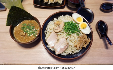 Tsukemen Japanese Ramen. Dry noodle with separate rich fish soup in black bowl.