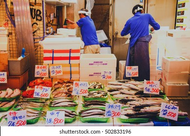 Tsukiji, Tokyo, Japan - October 24, 2016 : Japanese fishmonger preparing and packing fish into foam box at Tsukiji Fish Market in Tokyo, Japan. film style photo