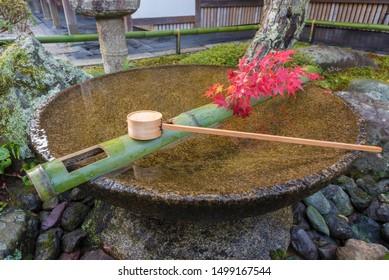 Tsukubai Water Fountain in Japanese Garden in Zuiganzan Enkouji Temple, Kyoto, Japan in autumn. With red maple leaves around the washbasin.