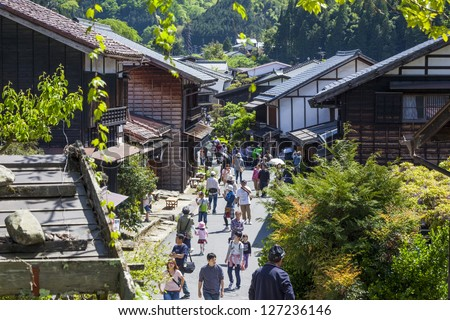 TSUMAGO, JAPAN - MAY 12 : Sightseers in Tsumago, Kiso Valley, Japan on 12th May 2012. The picturesque town is a popular tourist destination due to the rural setting and traditional wooden buildings.