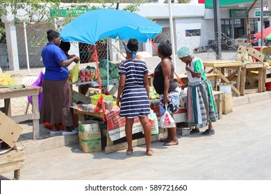 TSUMEB, GROOTFONTEIN, NAMIBIA, AFRICA - October 20, 2016. Young and elderly black African women buy fresh vegetables and female vendors sell food at traditional local street market. Small shop owners