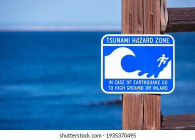 Tsunami Hazard Zone warning sign on the Pacific Ocean coast warn the public about possible danger after an earthquake. Blue ocean in background