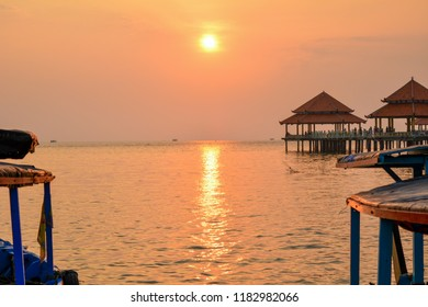 Tthe view of the sunset on the Jepara Kartini beach in Central Java between the boats that are leaning on the harbor