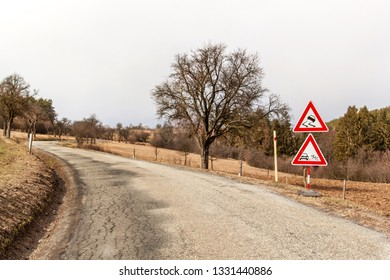 """Ttraffic sign """"Slippery Road"""" on the road background in Czech Republic. Warning sign concerning dangerous road surface.  Asphalt road in the countryside."""
