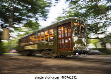A ttreetcar tram running through the leafy Garden District of New Orleans in a shadowy sunset motion blur