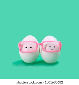 Ttwo eggs in pink glasses like Siamese twins. Funny character in kawaii style. Creative Easter decor. Minimum Easter concept
