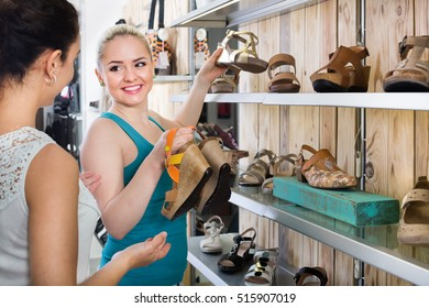 Ttwo glad young women selecting a shoes and chatting among the shelves