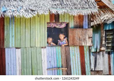 TUARAN, Sabah - DECEMBER 18, 2018 : Two siblings chat on the side of the window in Penimbawan water village, Tuaran, Sabah.