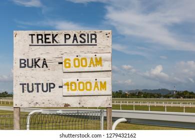 Tuaran, Sabah, Malaysia - November 28 2018: Information board, indicating the opening hours for crossing the race track at Royal Sabah Turf Club (malay: Kelab Lumba Kuda Diraja Sabah)