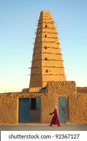 A tuareg man walking in front of the Agadez mud mosque