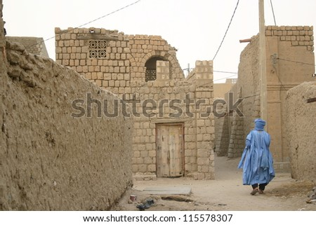 A Tuareg nomad of the Berber people wanders the muddy  back streets of Timbuktu, Mali