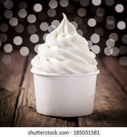 Tub of creamy vanilla or tangy lemon ice cream on an old wooden bar counter with a bokeh of festive party lights