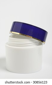 tub with a face cream with a dark blue cover on a white background