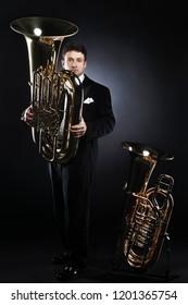 Tuba player brass instrument. Classical musician portrait. Man horn player.