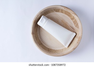 Tube with cream in wooden utensils on a white background