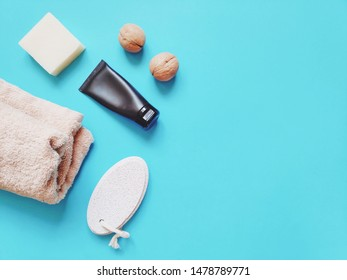 A tube of foot cream, walnuts, white soap, pumice and a beige towel