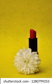 A tube of red lipstick with a white aster on a yellow background