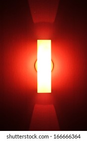 Tube of red neon light on textured wall