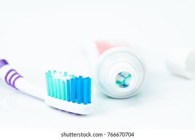 A tube of toothpaste and a toothbrush on white background closeup