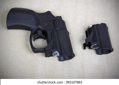 Tubeless doubly charged non-lethal pistol and holder with two bullets. Image with vignette