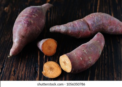 tubers of sweet potato or yams on a dark wooden background. Jewel Yams