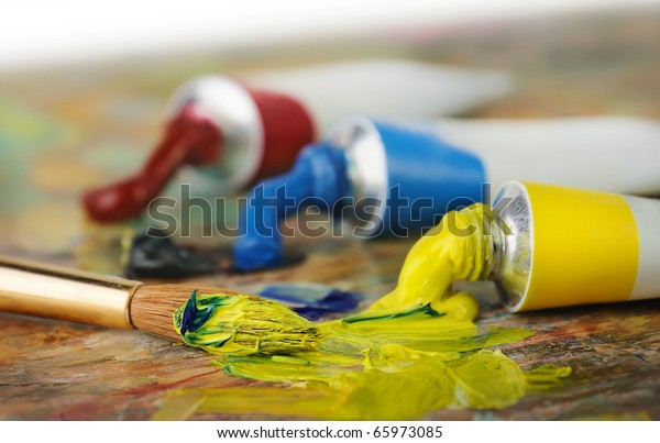 Tubes with acrylic or oil paint and brush over colorful artist's palette, selective focus