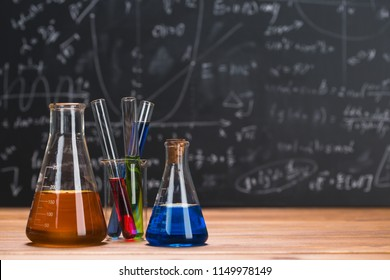 Tubes with chemical liquids stand on a wooden table on a chalkboard background with digital formulas
