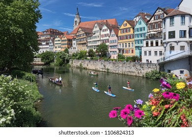 TUBINGEN, GERMANY - MAY 21, 2018: Historical houses at riverside of Neckar. Unknown people ride along the river on traditional punt boats and standup paddle boards, and have rest at the embankment.