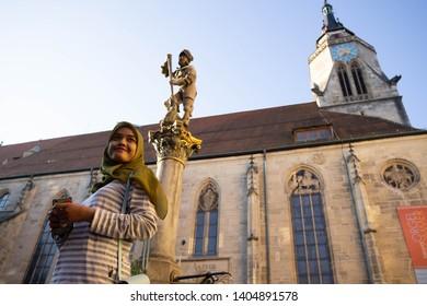 TUBINGEN/GERMANY:JULY 30 2018: A Muslim traveler woman looks happy, walking on the sidewalks of the city of Tubingen near the St. George's Collegiate Church