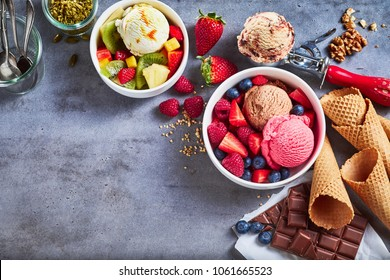Tubs of fresh fruit with ice cream and ingredients including, chocolate, berries, walnuts, pistachio and a metal scoop for serving on slate with copy space, top down view