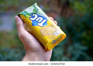 Tuc snack pack in male hand on a green trees background