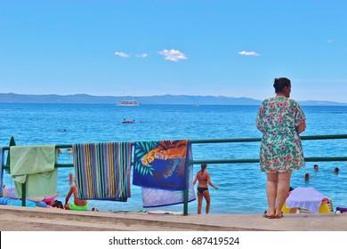 Tucepi, Croatia - July 27, 2017: People on the beach of Tucepi near Makarska, Croatia. South-Eastern Europe.