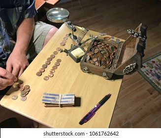Tucson, Arizona, USA, April 3, 2018: Man sorting 1-cent coins out of a treasure chest
