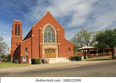 Tucson, Arizona, USA – April 30, 2018:  Red brick exterior of Grace Evangelical Lutheran Church in Tucson, Arizona with blue sky copy space,  stained glass windows and bell tower.