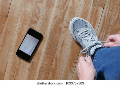 Tucson, Arizona, USA, February 13: Woman tying shoelace of sneakers with iPhone next to foot on wooden floor
