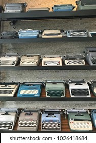 Tucson, Arizona, USA, February 16, 2018: Shelf with several rows of old typewriters in front of a wall printed with type