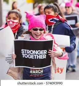 TUCSON, AZ - JANUARY 21: Happy trio of white and Latina girls holding protest signs at Women's March on Washington January 21, 2017 in Tucson, AZ, USA.