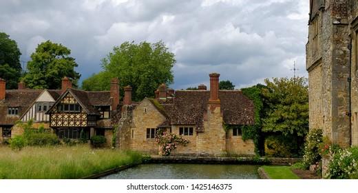 Tudor houses with stone walls across the moat from Hever Castle, Edenbridge in Sevenoaks district of Kent, England, UK. June 15th
