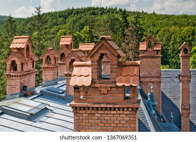 Tudor styled red brick chimneys on the top of a modern castle hotel with green mountains in the background