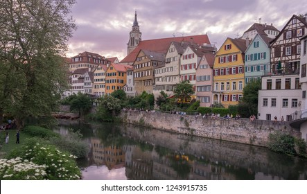 Tuebingen in the Stuttgart city ,Germany Colorful house in riverside and blue sky.  Beautiful old city in Europe. People sitting on the wall. Boats wooden moored at dock.