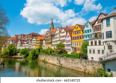 Tuebingen in the Stuttgart city ,Germany Colorful house in riverside and blue sky. Beautiful old city in Europe.People sitting on the wall.Boats wooden moored at dock.