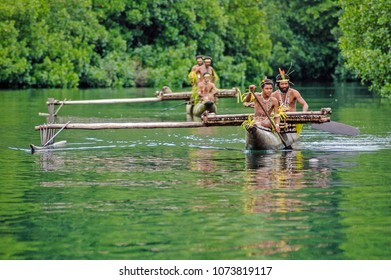 "Tufi, Oro Province/ Papua New Guinea. March 23 2009:  Canoes paddle out to meet visitors from a small expedition ship. The men wear ""bilas"", body ornamentation - feathers, shells and colorful plants"