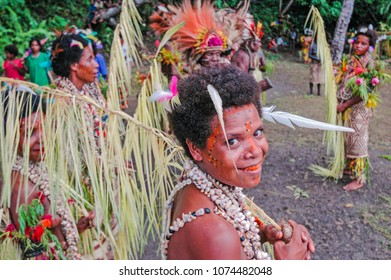 "Tufi, Oro Province/ Papua New Guinea. March 23 2009:  A young dancer smiles, her teeth stained red, from chewing betel nut. She wears ""bilas"" - ornamentation consisting of shells, feathers and flowers"