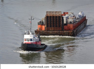 Tug Boat and Barge, Fraser River. A tugboat maneuvers a barge up the Fraser River. Near Vancouver, British Columbia, Canada.