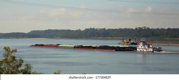 Tug boat and barges of petroleum oil passes under the Vicksburg Bridge along the Mississippi River