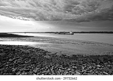 tug boat going by during angry weather at low tide